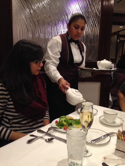 Lupe serves tea to Yasmin