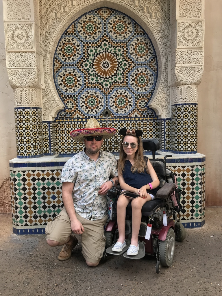 A young woman in an electric wheelchair sits next to a young man with a colorful sombrero kneeling next to her, in front of a colorful mosaic fountain