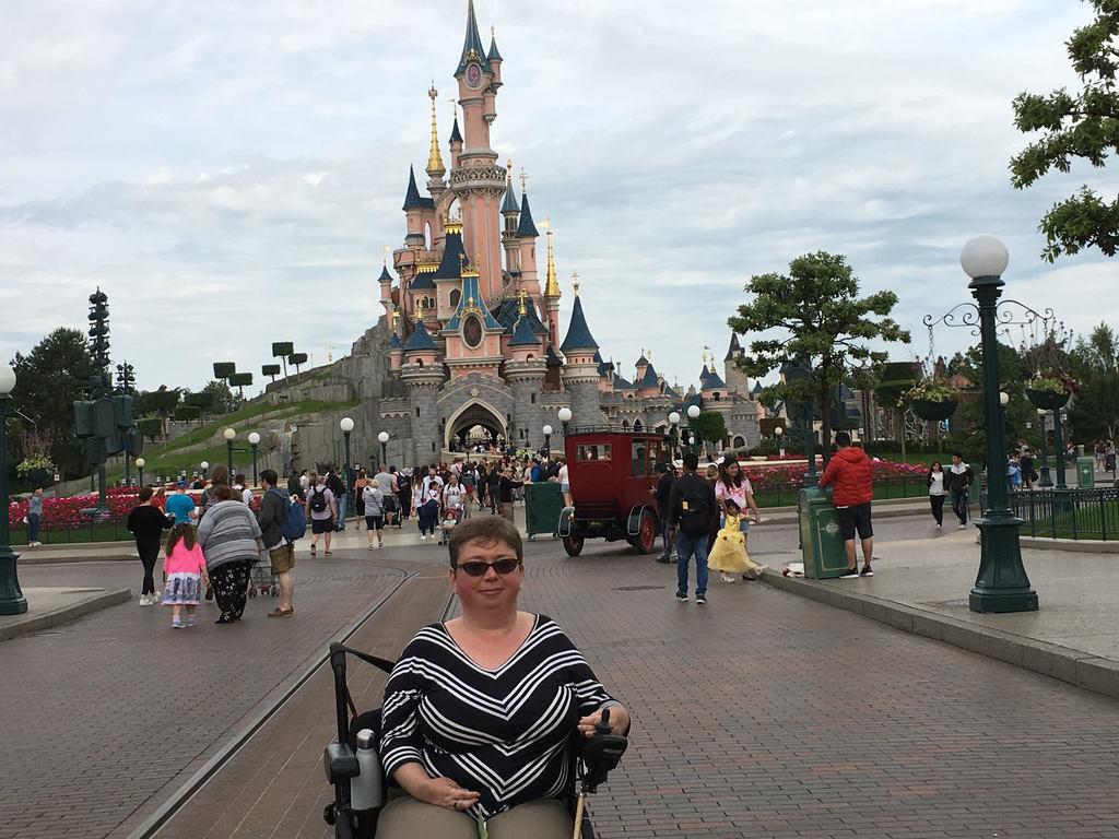 Woman in wheelchair in front of Disneyland Paris castle