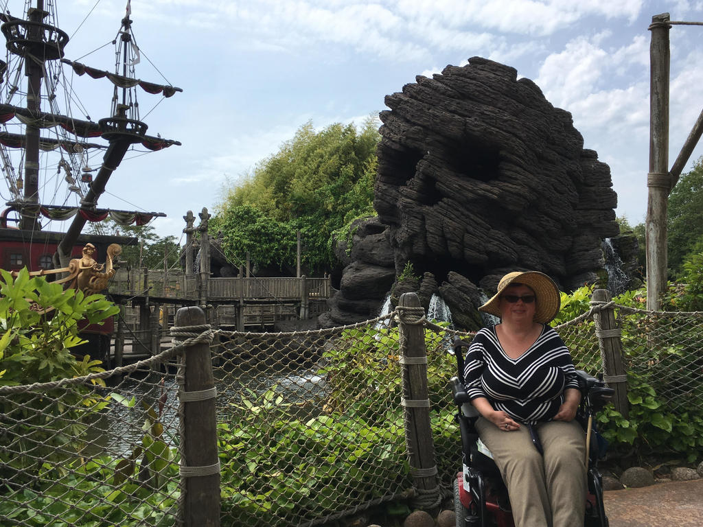 Author in wheelchair in front of giant pirate ship and skull cave