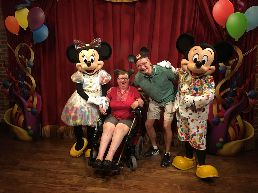 Author and husband wearing ears with Minnie and Mickey