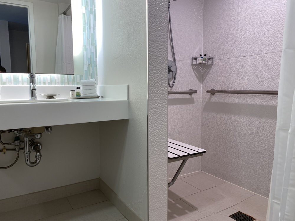 Accessible bathroom with roll-up sink and transfer shower
