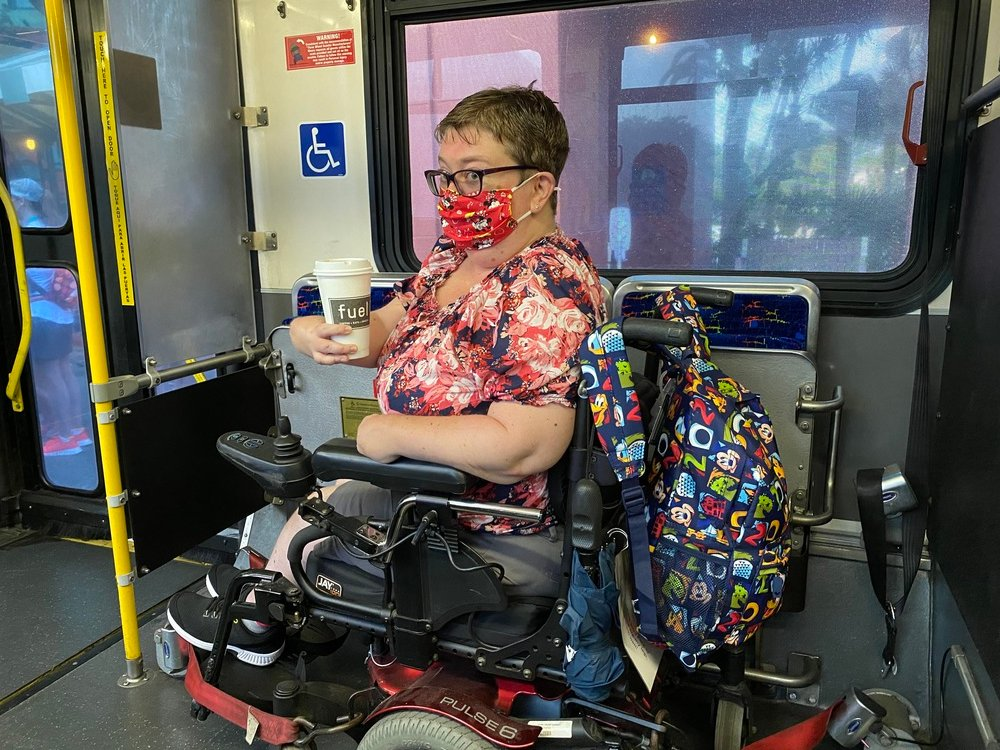 Author parked and secured on bus in her motorized wheelchair